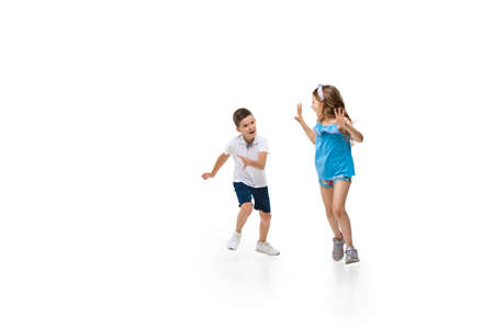 Happy kids, little and emotional caucasian boy and girl jumping and running isolated on white background. Look happy, cheerful, sincere. Copyspace for ad. Childhood, education, happiness concept.