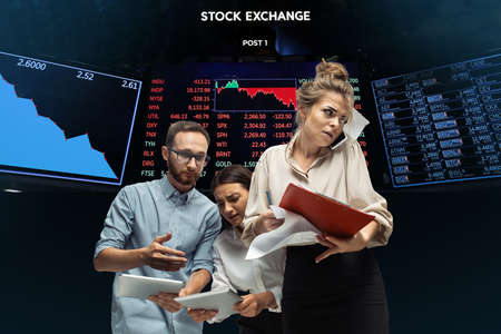 Intense. Nervous tensioned investors analyzing crisis stock market with charts of falling stock exchange. Defaulted, crisis of exchange markets and funds. Overly concerned people with gadgets, papers.