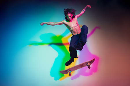 Skateboarder doing a trick isolated on studio background in colorful neon light. Young man shirtless riding and skateboarding in motion. Concept of leisure activity, sport, extreme, hobby and motion.