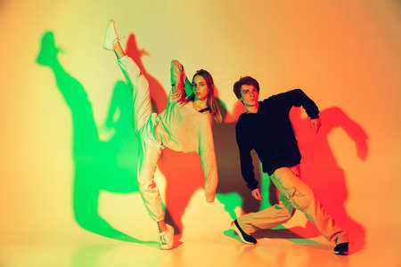 Young man and woman, couple dancing hip-hop, street style isolated on studio background in colorful neon light. Fashion and motion, youth, music, action concept. Trendy clothes. Copyspace for ad. 免版税图像