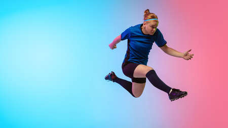 High jumping. Female soccer, football player training in action isolated on gradient studio background in neon light. Concept of motion, action, ahievements, healthy lifestyle. Youth culture.