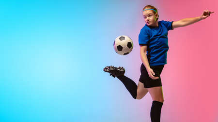 Bouncing ball. Female soccer, football player training in action isolated on gradient studio background in neon light. Concept of motion, action, ahievements, healthy lifestyle. Youth culture.