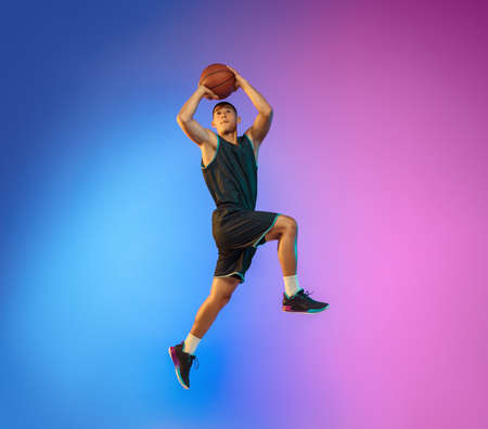 Winner. Young basketball player in action, motion in high jump on gradient background in neon. Concept of sport, movement, energy and dynamic, healthy lifestyle. Training, practicing, trendy colors.