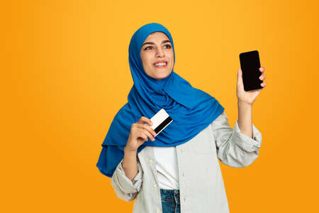 Showing phone and card. Young muslim woman isolated on yellow studio background. Stylish, trendy and beautiful female model. Human emotions, facial expression, sales, ad, shopping concept. Copyspace.