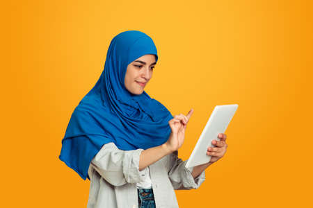 Holding tablet, scrolling. Young muslim woman on yellow studio background. Stylish, trendy and beautiful female model. Human emotions, facial expression, sales, ad, shopping concept. Copyspace.