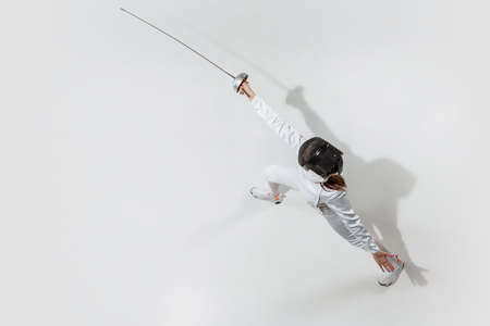 Champion. Teen girl in fencing costume with sword in hand on white background. Top view. Young female model practicing and training in motion, action. Copyspace. Sport, youth, healthy lifestyle. Banque d'images