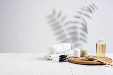 Beautiful spa composition on massage table in wellness center, copyspace. Accessories for relaxing treatments and personal care. Towels, oils, serum, sea salts and scrubs. Decorative candles. Copyspace. Standard-Bild