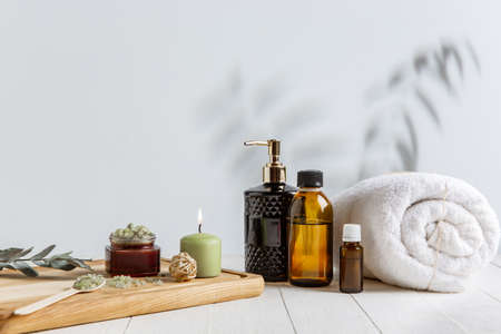Beautiful spa composition on massage table in wellness center, copyspace. Accessories for relaxing treatments and personal care. Towels, oils, serum, sea salts and scrubs. Decorative candles. Standard-Bild