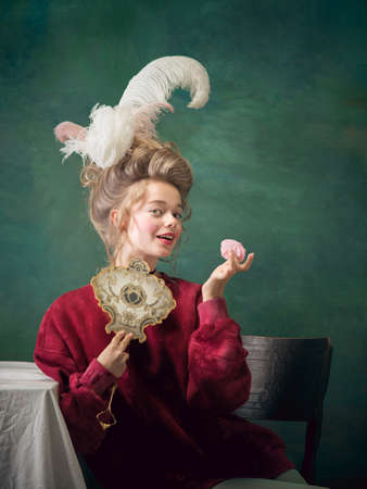 Sweet marshmallow. Young woman as Marie Antoinette isolated on dark green background. Retro style, comparison of eras concept. Beautiful female model like classic historical character, old-fashioned. Stock fotó
