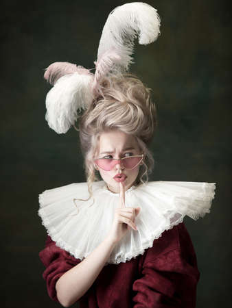 Stylish eyewear. Young woman as Marie Antoinette isolated on dark green background. Retro style, comparison of eras concept. Beautiful female model like classic historical character, old-fashioned. Stock fotó