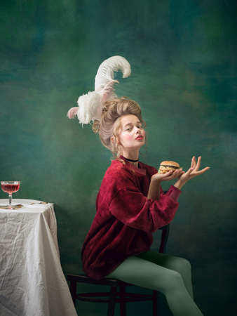 Burger queen. Young woman as Marie Antoinette isolated on dark green background. Retro style, comparison of eras concept. Beautiful female model like classic historical character, old-fashioned.