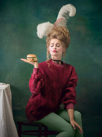 Such a welcome burger. Young woman as Marie Antoinette on dark green background. Retro style, comparison of eras concept. Beautiful female model like classic historical character, old-fashioned.