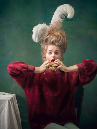 Such a tasty burger. Young woman as Marie Antoinette on dark green background. Retro style, comparison of eras concept. Beautiful female model like classic historical character, old-fashioned. Stock fotó