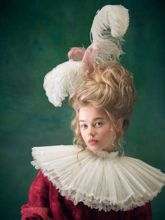 Stylish and trendy. Young woman as Marie Antoinette on dark green background. Retro style, comparison of eras concept. Beautiful female model like classic historical character, old-fashioned.