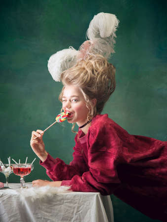 Sweet candy, playful mood. Young woman as Marie Antoinette on dark green background. Retro style, comparison of eras concept. Beautiful female model like classic historical character, old-fashioned.