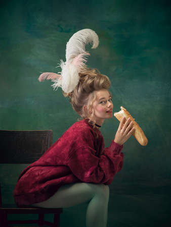 Baguette eating, tasty. Young woman as Marie Antoinette on dark green background. Retro style, comparison of eras concept. Beautiful female model like classic historical character, old-fashioned.