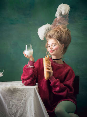 Baguette eating with milk. Young woman as Marie Antoinette on dark green background. Retro style, comparison of eras concept. Beautiful female model like classic historical character, old-fashioned.