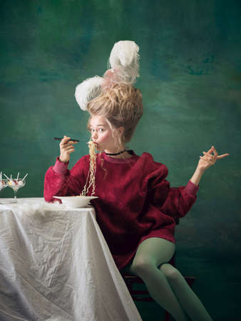 Instant noodles for queen. Young woman as Marie Antoinette on dark green background. Retro style, comparison of eras concept. Beautiful female model like classic historical character, old-fashioned.
