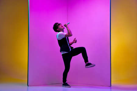 Celebrity. Young male musician, singer performing on pink-orange background in neon light. Concept of music, hobby, festival, entertainment, emotions. Joyful party host, singer, portrait of artist.