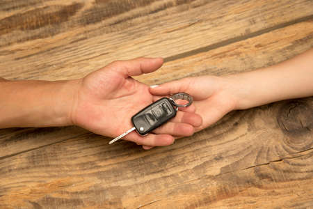 Human hands holding car key isolated on wooden background with copyspace. Selling a transport, agreement, new automobile, leasing for customer. Negative space for advertising. Banco de Imagens