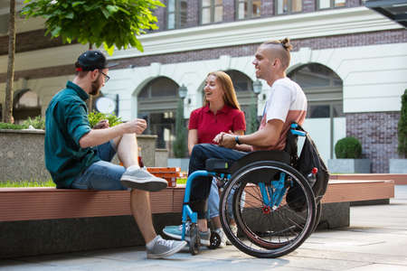 Group of friends taking a stroll on citys street in summer day. Disabled, handicapped man with his friends having fun. Inclusion and diversity concept, normal lifestyle of special groups of society.