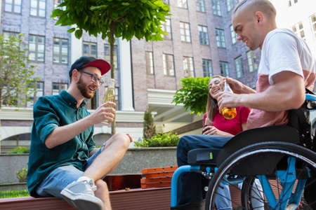 Beer time. Group of friends taking a stroll on citys street in summer day. Handicapped man with his friends having fun. Inclusion and diversity concept, normal lifestyle of special groups of society.