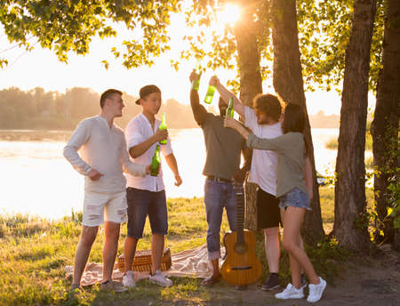 Youth. Group of friends clinking beer bottles during picnic at the beach in sunshine. Lifestyle, friendship, having fun, weekend and resting concept. Looks cheerful, happy, celebrating, festive. 免版税图像