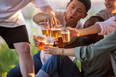 Party. Group of friends clinking beer glasses during picnic at the beach in sunshine. Lifestyle, friendship, having fun, weekend and resting concept. Looks cheerful, happy, celebrating, festive.