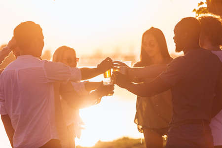Evening. Group of friends clinking beer glasses during picnic at the beach in sunshine. Lifestyle, friendship, having fun, weekend and resting concept. Looks cheerful, happy, celebrating, festive. Stock Photo