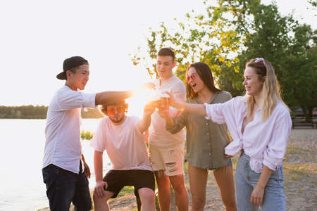 Sunset. Group of friends clinking beer glasses during picnic at the beach in sunshine. Lifestyle, friendship, having fun, weekend and resting concept. Looks cheerful, happy, celebrating, festive.