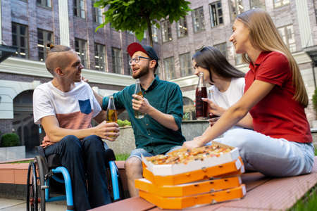 Pizza time. Group of friends taking a stroll on citys street in summer day. Handicapped man with his friends having fun. Inclusion and diversity concept, normal lifestyle of special groups of society.