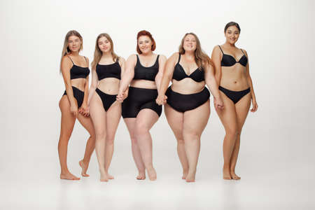 In love with myself. Portrait of beautiful young women with different shapes posing on white background. Happy female models. Concept of body positive, beauty, fashion, style, feminism. Diversity. Standard-Bild