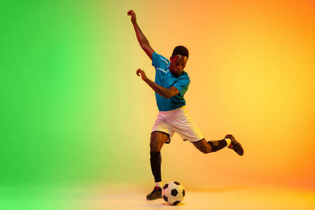 Leader. African-american male soccer, football player training in action isolated on gradient studio background in neon light. Concept of motion, action, ahievements, healthy lifestyle. Youth culture.