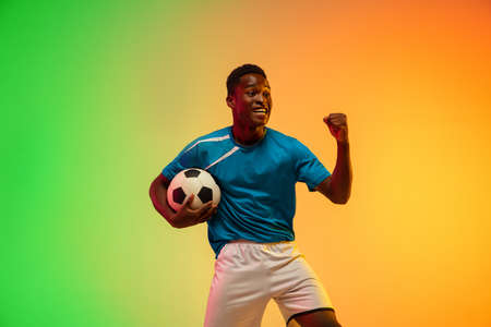 Unstoppable. African-american male soccer, football player training in action isolated on gradient studio background in neon light. Concept of motion, action, ahievements, healthy lifestyle. Youth culture.