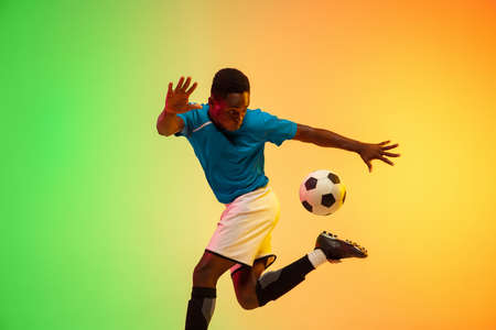 High jumping. Male soccer, football player training in action isolated on gradient studio background in neon light. Concept of motion, action, ahievements, healthy lifestyle. Youth culture. Reklamní fotografie