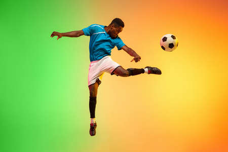 High jumping. Male soccer, football player training in action isolated on gradient studio background in neon light. Concept of motion, action, ahievements, healthy lifestyle. Youth culture.