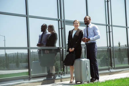 Presentation. Meeting of young business partners after arriving to end point of business trip. Man and woman walking against glass wall background of modern building. Concept of business, finance, ad.