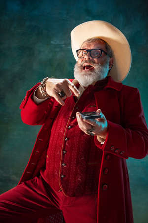 Pointing on phone. Modern stylish Santa Claus in red fashionable suit and cowboy's hat on dark background. Looks like a rockstar. New Year and Christmas eve, celebration, holidays, winter's mood, fashion.