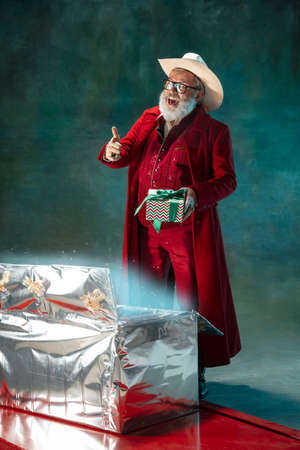 Santas offers. Modern stylish Santa Claus in red fashionable suit and cowboys hat on dark background. Looks like a rockstar. New Year and Christmas eve, celebration, holidays, winters mood, fashion. Stock Photo