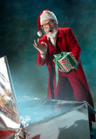 Magic glowing. Modern stylish Santa Claus in red fashionable suit and cowboys hat on dark background. Looks like a rockstar. New Year and Christmas eve, celebration, holidays, winters mood, fashion.