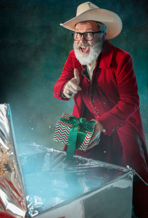 Gifts for 2021. Modern stylish Santa Claus in red fashionable suit and cowboys hat on dark background. Looks like a rockstar. New Year and Christmas eve, celebration, holidays, winters mood, fashion.