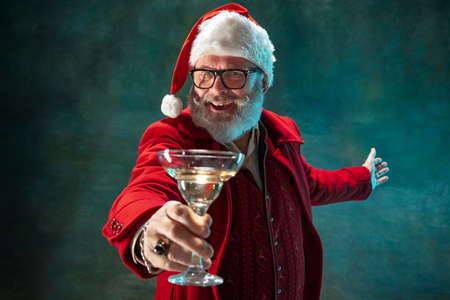Cheers. Modern stylish Santa Claus in red fashionable suit and cowboys hat on dark background. Looks like a rockstar. New Year and Christmas eve, celebration, holidays, winters mood, fashion. Stock Photo