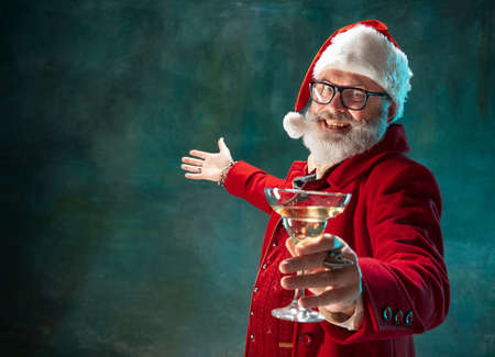 Lets party. Modern stylish Santa Claus in red fashionable suit and cowboys hat on dark background. Looks like a rockstar. New Year and Christmas eve, celebration, holidays, winters mood, fashion.