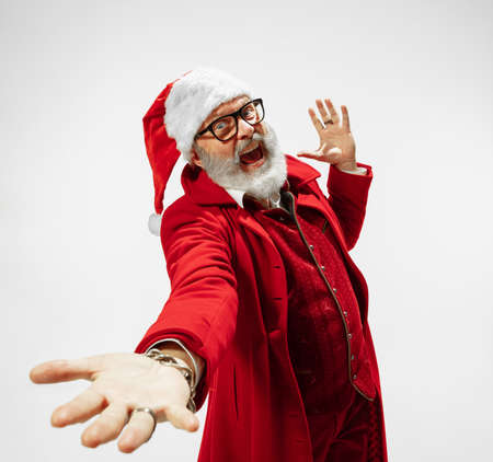 Dancing man. Modern stylish Santa Claus in red fashionable suit isolated on white background. Looks like a rockstar. New Year and Christmas eve, celebration, holidays, winters mood, fashion.