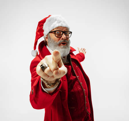 Choosing you. Modern stylish Santa Claus in red fashionable suit isolated on white background. Looks like a rockstar. New Year and Christmas eve, celebration, holidays, winters mood, fashion. Stock Photo