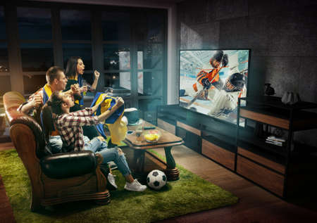 Group of friends watching hockey match, sport together. Emotional men and women cheering for favourite team, look on goal and fighting for win. Concept of friendship, leisure activity, emotions.