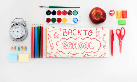 Colorful school supplies corner border over a white background with words Back to school. Pencils, paints, scissors, stickers. Education, school time, childhood concept. Copyspace, ready for ad.