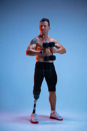Athlete with disabilities or amputee isolated on blue studio background. Professional male sportsman with leg prosthesis training with weights in neon. Disabled sport and overcoming, wellness concept.