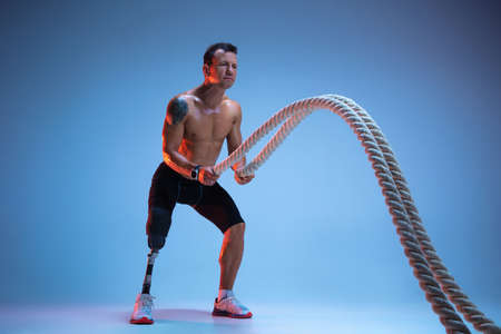 Athlete with disabilities or amputee isolated on blue studio background. Professional male sportsman with leg prosthesis training with ropes in neon. Disabled sport and overcoming, wellness concept. Stock Photo