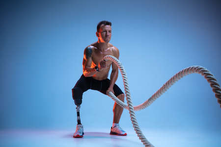 Athlete with disabilities or amputee isolated on blue studio background. Professional male sportsman with leg prosthesis training with ropes in neon. Disabled sport and overcoming, wellness concept.
